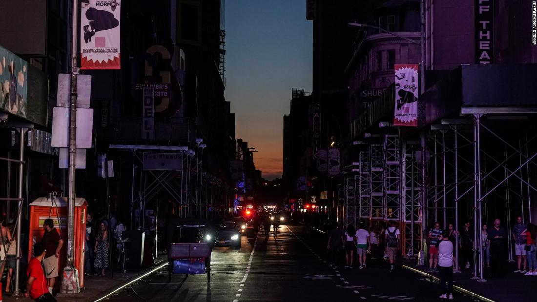 Dark buildings along a dark street are seen near the Times Square area.