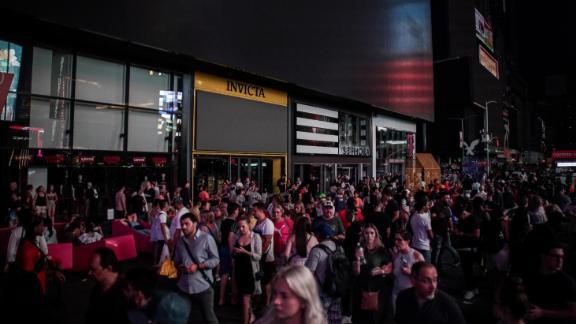 People walk along a dark street near Times Square.