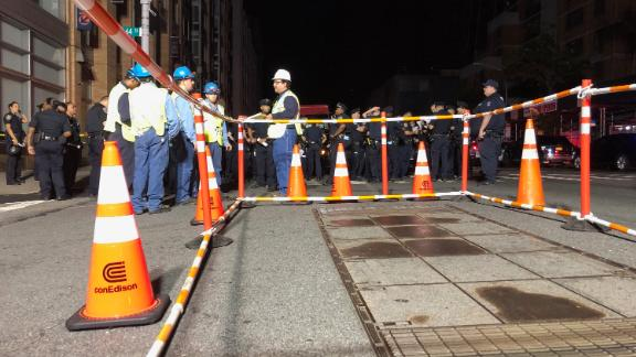 Con Edison workers stand around a barricaded transformer cover.