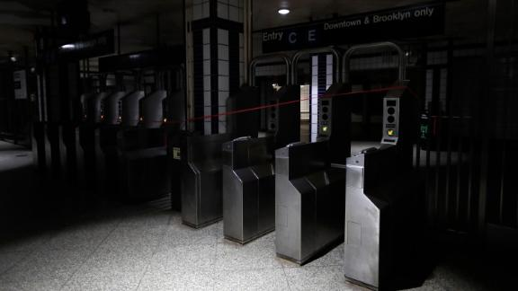 An entrance to the C and E trains at the 50th Street Subway Station is dimly lit.