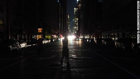 People walk down the streets during a major power outage affecting parts of New York City on July 13, 2019. - Subway stations plunged into darkness and the billboards of Times Square suddenly flicked off as New York's Manhattan was hit by a power outage on Saturday. About 42,000 customers lost electricity in the early evening, according to the Con Edison utility, which did not give a reason for the cut. (Photo by TIMOTHY A. CLARY / AFP)        (Photo credit should read TIMOTHY A. CLARY/AFP/Getty Images)