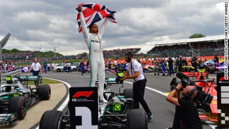 Mercedes' British driver Lewis Hamilton (C) waves the Union flag as he celebrates in parc ferme after victory in the British Formula One Grand Prix at the Silverstone motor racing circuit in Silverstone, central England, on July 14, 2019. - Lewis Hamilton extended his lead at the top of the Formula One championship on Sunday after winning the British Grand Prix for a record sixth time. (Photo by Andrej ISAKOVIC / AFP)        (Photo credit should read ANDREJ ISAKOVIC/AFP/Getty Images)
