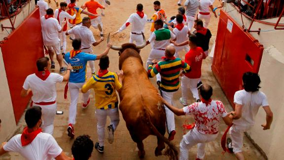 Revellers and a fighting bull face off in the bullring during the final running of the bulls at the San Fermin Festival Sunday.