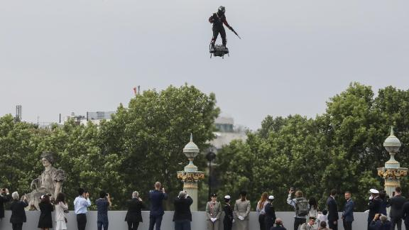 """TOPSHOT - Zapata CEO Franky Zapata flies a jet-powered hoverboard or """"Flyboard"""" prior to the Bastille Day military parade down the Champs-Elysees avenue in Paris on July 14, 2019. (Photo by ludovic MARIN / AFP)        (Photo credit should read LUDOVIC MARIN/AFP/Getty Images)"""