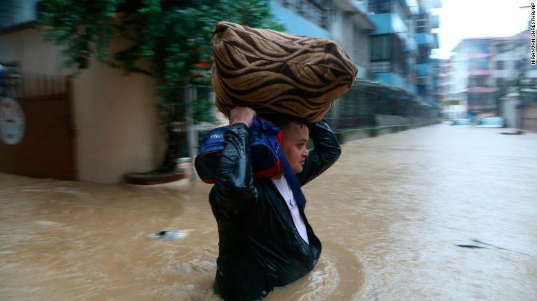 A Nepalese man wades through a flooded street in Kathmandu, Nepal, on July 12, 2019.