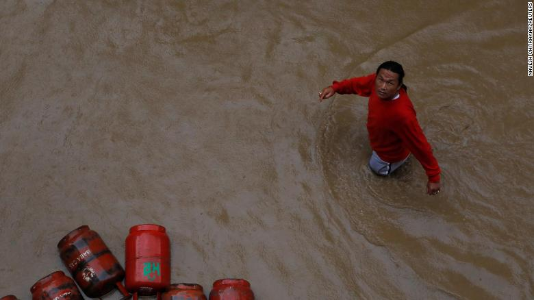 A man walks past gas cylinders in a flooded colony in Kathmandu, Nepal on July 12, 2019.