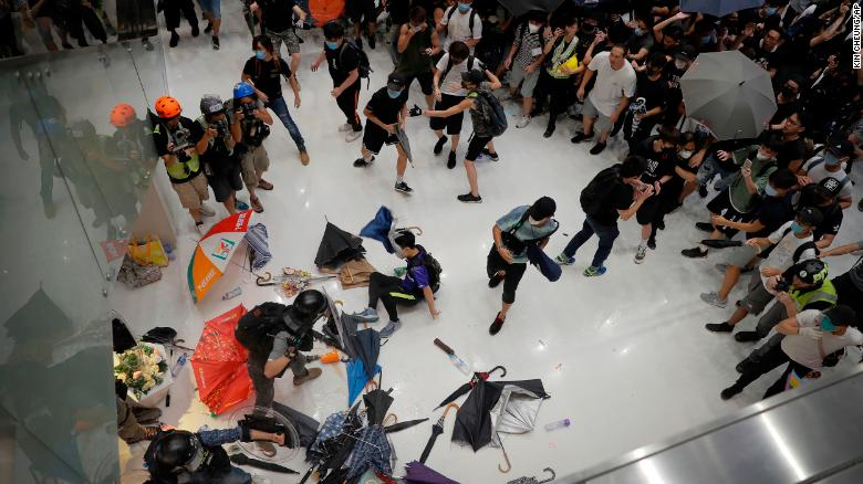 Policemen scuffle with protesters inside a shopping mall in Sha Tin District in Hong Kong on July 14, 2019.
