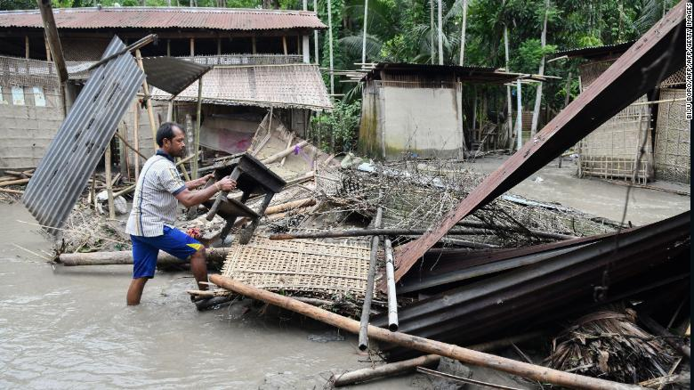An Indian woman near the debris of her house in the state of Assam, on July 13, 2019.