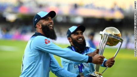 Moeen Ali of England and Adil Rashid of England parade the World Cup trophy.