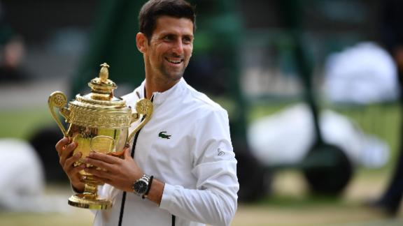 Serbia's Novak Djokovic holds the winner's trophy during the presentation after beating Switzerland's Roger Federer during their men's singles final on day thirteen of the 2019 Wimbledon Championships at The All England Lawn Tennis Club in Wimbledon, southwest London, on July 14, 2019. (Photo by Daniel LEAL-OLIVAS / AFP) / RESTRICTED TO EDITORIAL USE        (Photo credit should read DANIEL LEAL-OLIVAS/AFP/Getty Images)