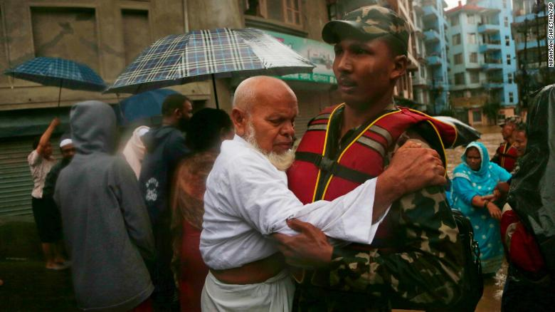 A Nepalese soldier moves an elderly man to a safer area in Kathmandu on July 12, 2019.