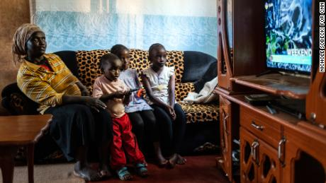 StarTimes subscriber Purity Njambi (34) watches television with her children [left to right] James Ngugi (3), Margaret Wahu (8) and Agnes Wambui (8), in their home in Ndumbuini village on the outskirts of Kenya's capital Nairobi, on April 5, 2019. 