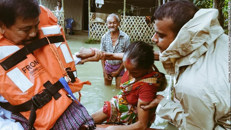 India's National Disaster Response Force evacuate people in flooded parts of Assam state.