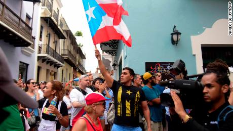 A man waves a Puerto Rican flag during a protest Sunday near La Fortaleza governor's residence in San Juan.