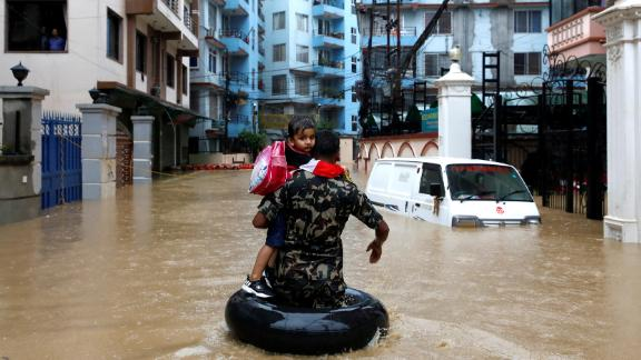 A member of Nepalese army carrying a child walks along the flooded colony in Kathmandu, Nepal on July 12, 2019.