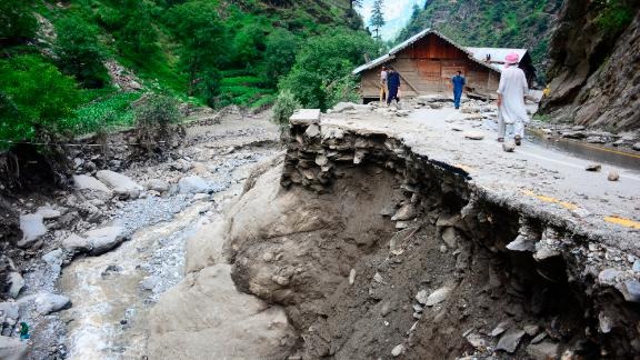 Villagers walk along a road washed away by heavy flooding in Neelum Valley of Pakistani controlled Kashmir, Monday, July 15, 2019. Pakistan says many people are missing and feared dead after heavy rains triggered flash floods in Pakistani-controlled Kashmir. Ahmed Raza Qadri, the Pakistani minister for disaster management in the disputed territory, says the flooding late on Sunday also caused much destruction and damage in the village of Lesswa in Neelum Valley.