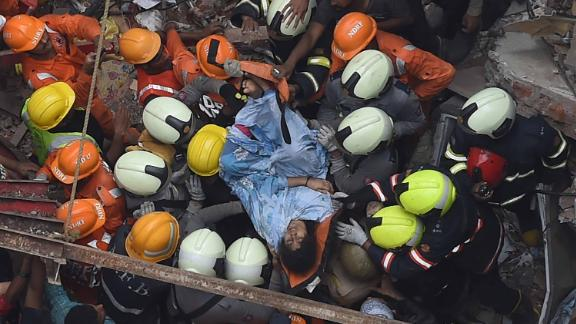 Emergency personnel rescue a survivor from the rubble.
