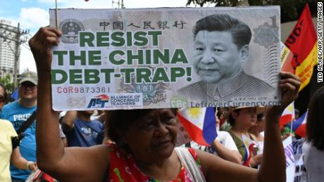 An anti-China protester raises a placard with a portrait of Chinese President Xi Jinping during a protest in front of the Chinese consular office in the financial district of Manila on April 9.
