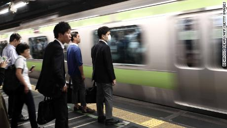 People wait for the train at a subway station in Tokyo.
