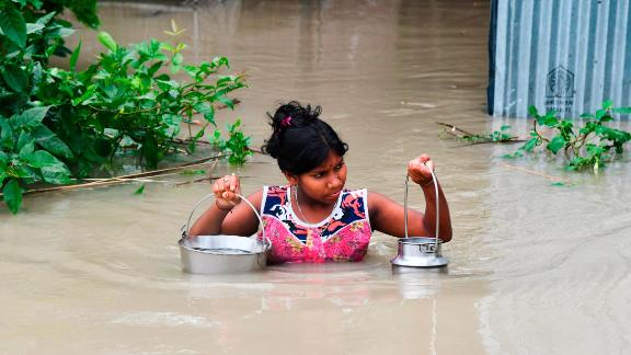 An Indian girl carries drinking water as she wades through flood waters in India