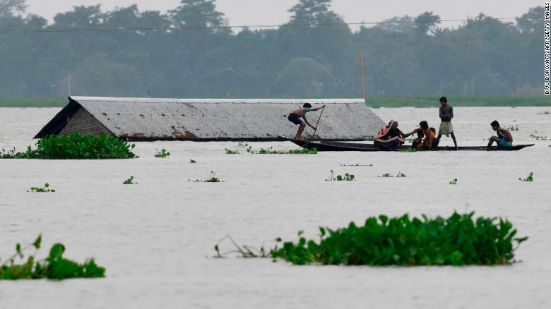img Villagers travel on a boat near a submerged house in the Morigaon district of India's Assam state on July 15, 2019.