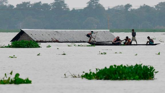 Villagers travel on a boat near a submerged house in the Morigaon district of India