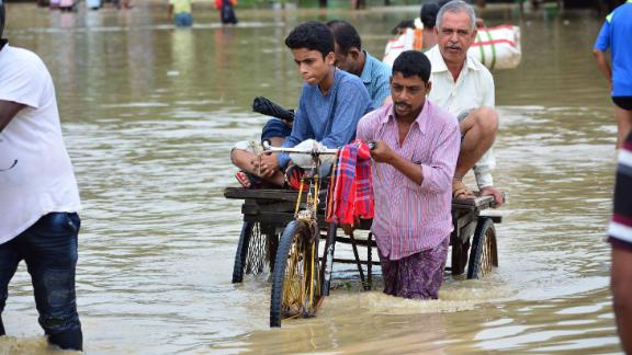 An Indian rickshaw puller transports commuters on a flooded street in the Indian state of Tripura, on July 14, 2019.