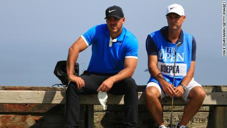 Brooks Koepka and caddie Ricky Elliott rest during a practice round at Royal Portrush.
