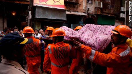 Rescuers carry the body of a victim at the scene in a crowded neighborhood of Mumbai.