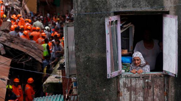 A woman watches from a window as rescuers work at the site of the collapse.