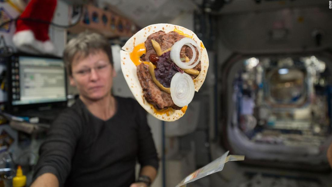 Astronaut Peggy Whitson and her cheeseburger wrapped in a tortilla are shown on the International Space Station. Since the mid '80s, flour tortillas have been a staple bread item in space that provides an almost crumble-free solution.