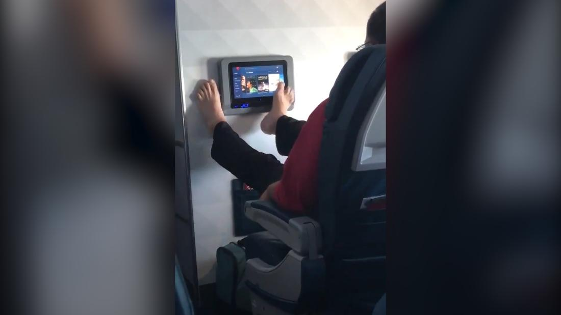 Airline passenger uses TV with his bare feet