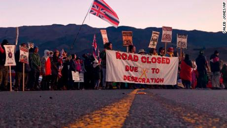 Demonstrators gather to block a road at the base of Hawaii's tallest mountain, Monday, July 15, 2019.