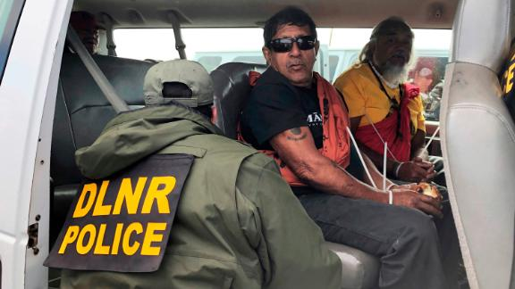 Officers from the Hawaii Department of Land and Natural Resources arrest protesters, many of them elderly.