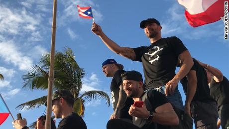 Ricky Martin pans a small Puerto Rican flag as he joins the protest in Puerto Rico.