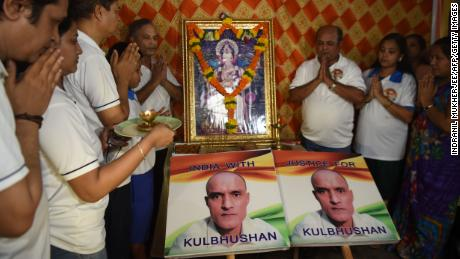 Indian residents in Mumbai offer prayers next to placards showing Kulbhushan Jadhav, an Indian national convicted of spying in Pakistan, July 17, 2019.