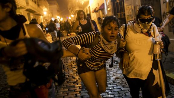 A woman is assisted in the streets after demonstrators clashed with police on Wednesday, July 17.