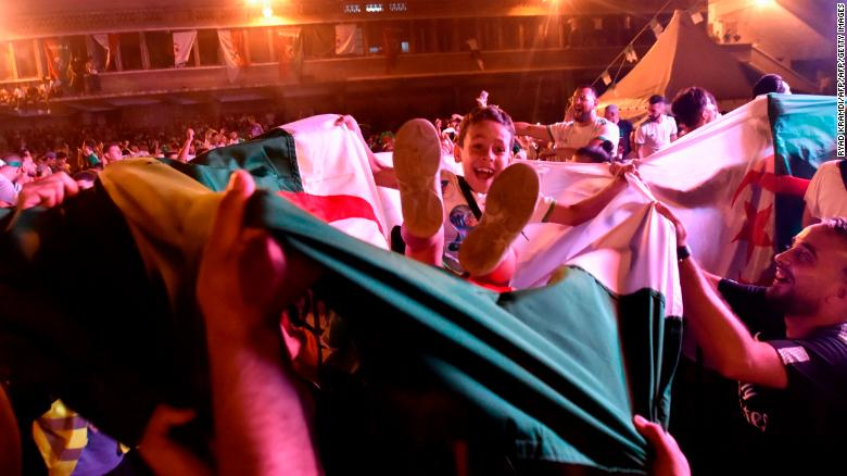 A young Algeria fan celebrates the victory that took the Fennec Foxes to a first AFCON final since 1990.