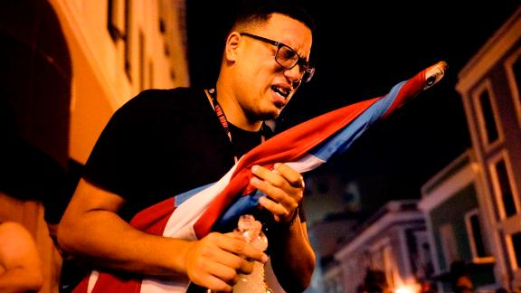 A protester reacts after being sprayed by tear gas in San Juan.