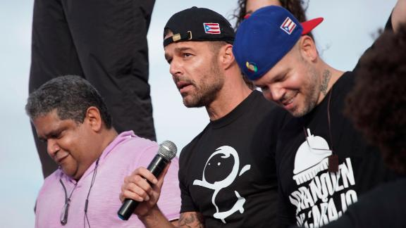 Ricky Martin holds a microphone during the march on July 17. At right is rapper Rene Perez, aka Residente.