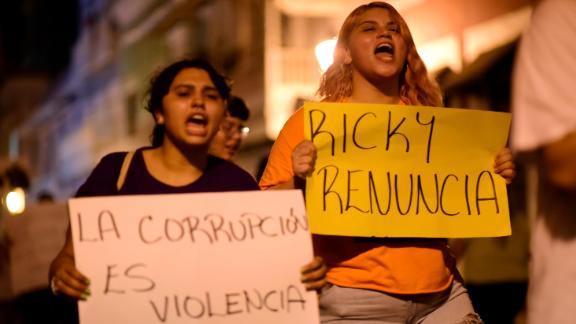 """Demonstrators hold signs that say """"Corruption is violence"""" and """"Ricky resign"""" while protesting near the executive mansion on Thursday, July 11."""