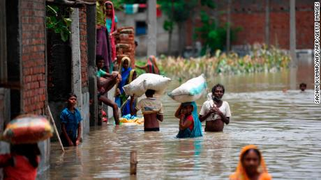 Indian residents in the state of Bihar wade along a flooded street carrying their belongings on July 17, 2019.