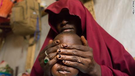 "Falamatu, 35, with her son. She gave up her 12 year old daughter, Innakaru to marry a Boko Haram foot soldier. ""The insurgents had seized my hometown Bama in Borno State. I live in regret, I pray my daughter Innakaru is safe and will forgive me""- Maiduguri, 2018"