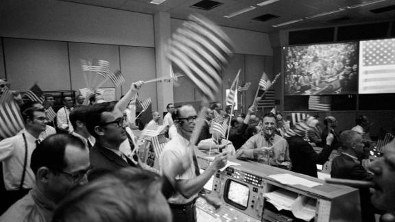 verall view of the Mission Operations Control Room in the Mission Control Center at the Manned Spacecraft Center showing the flight controllers celebrating the successful conclusion of the Apollo 11 lunar landing mission on Jul 24, 1969.Credits: NASA