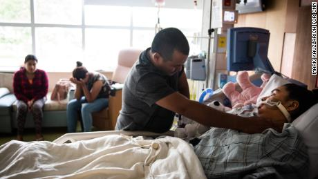 Miguel Gámez, father of Heydi Nallely Gámez Garcia, touches the bruises on his daughter's neck and his sister Jessica Gámez Garcia cries in the background as Heydi lays on life support in Cohen Children's Medical Center in Queens, NY on July 17, 2019. CREDIT: Mark Kauzlarich for CNN