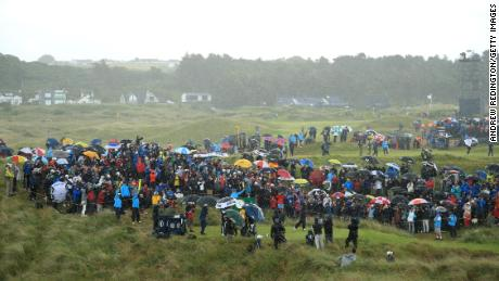 Tiger Woods drives off the seventh tee in a deluge.