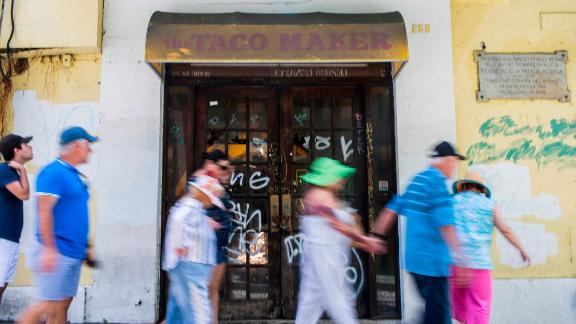 Tourists walk past a closed taco restaurant in San Juan.