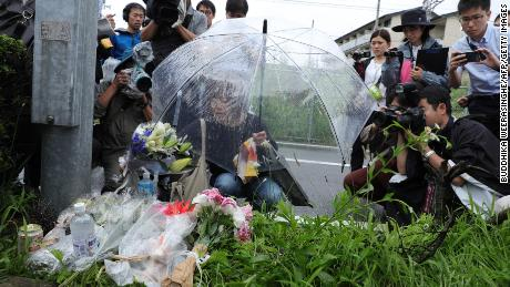 A woman pays her respects next to flowers and tributes laid at the scene of the Kyoto Animation fire.