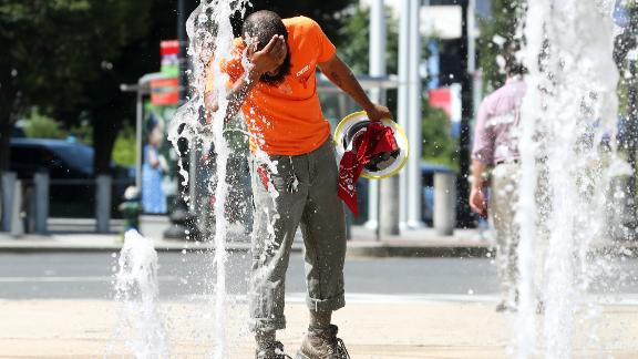 A construction worker stops to cool off in the water fountains at Canal Park in Washington.