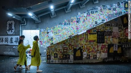 "People walk in front of a so-called ""Lennon Wall"" where messages of support have been left for anti-extradition bill protesters on July 1, 2019 in Hong Kong."
